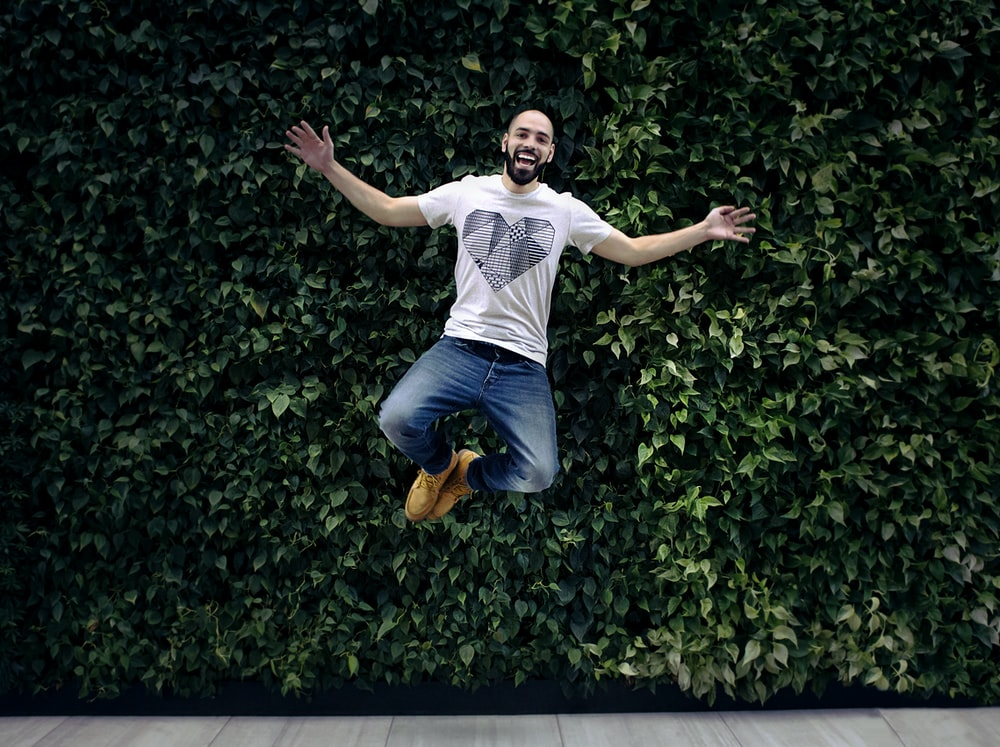 man wearing t-shirt and jeans jumpshot in front of a green hedge