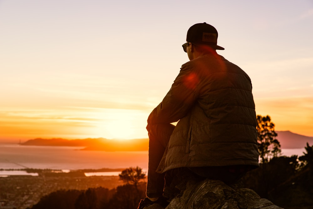 man sitting on rock looking at sunrise