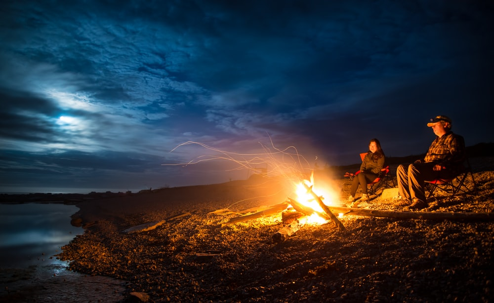 man and woman standing near bonfire on seashore during night