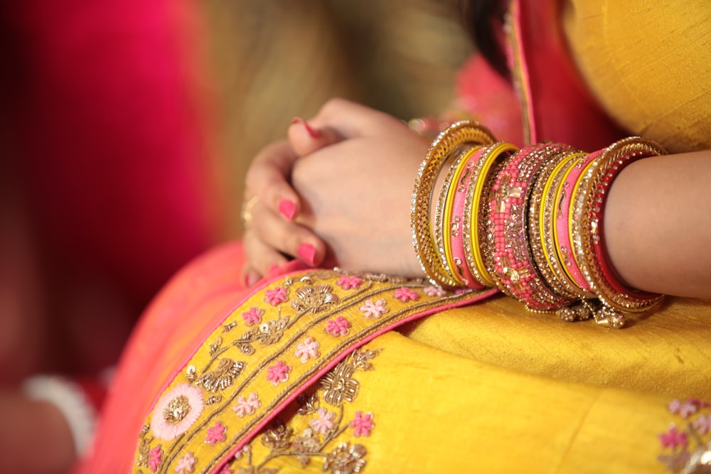 person wearing yellow sari dress holding both hands
