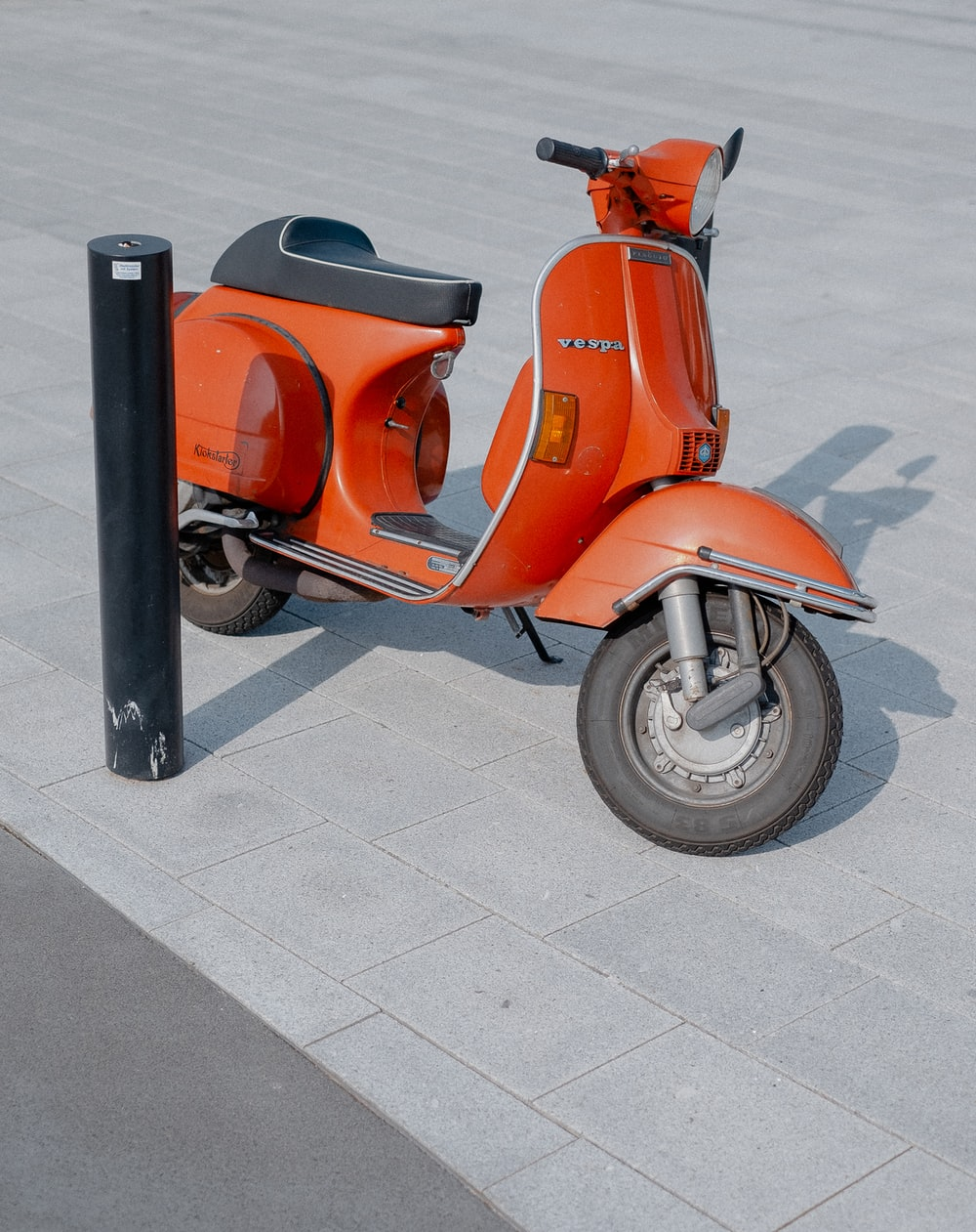red and black motor scooter on gray pathway