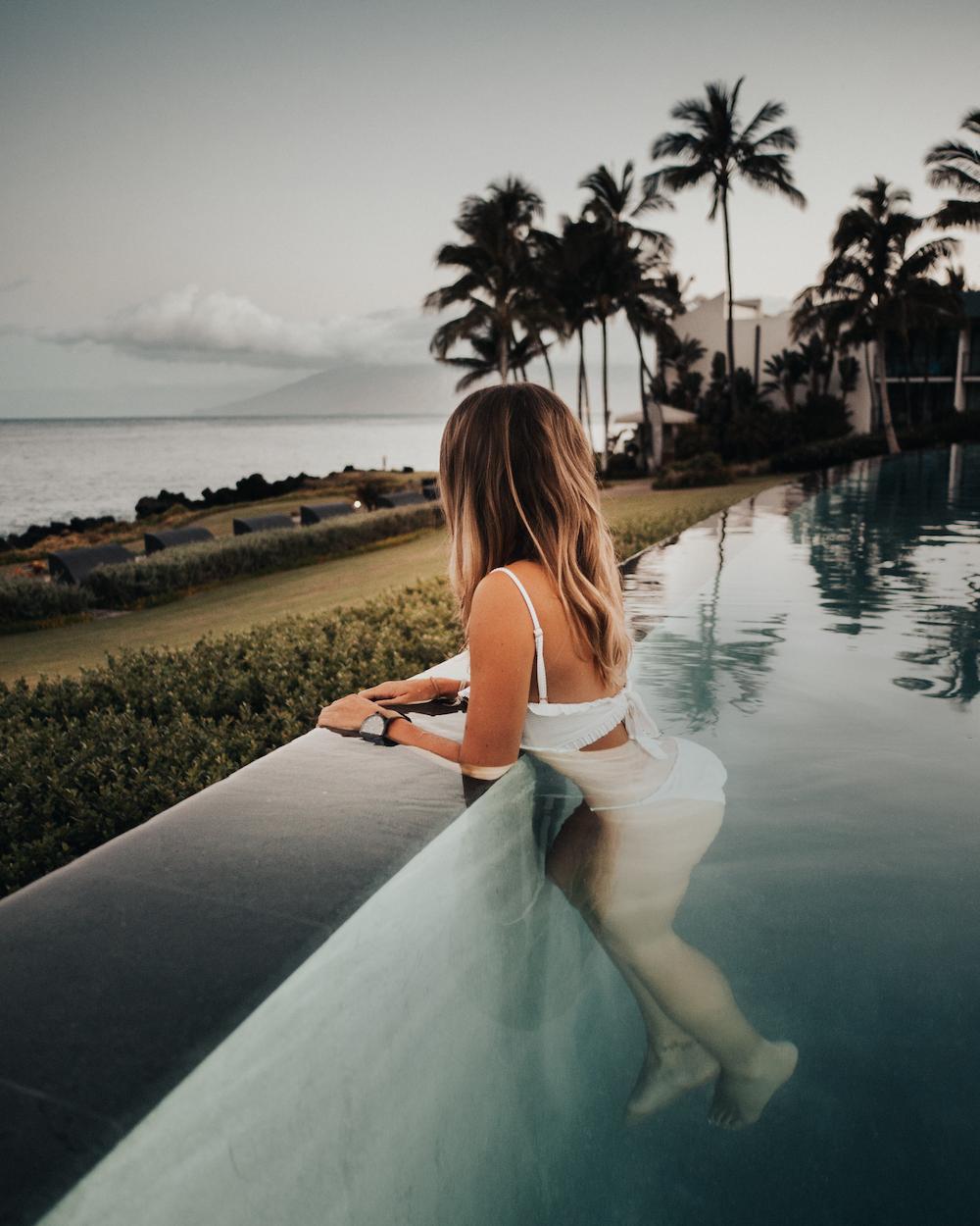 woman wearing white bikini in pool during daytime