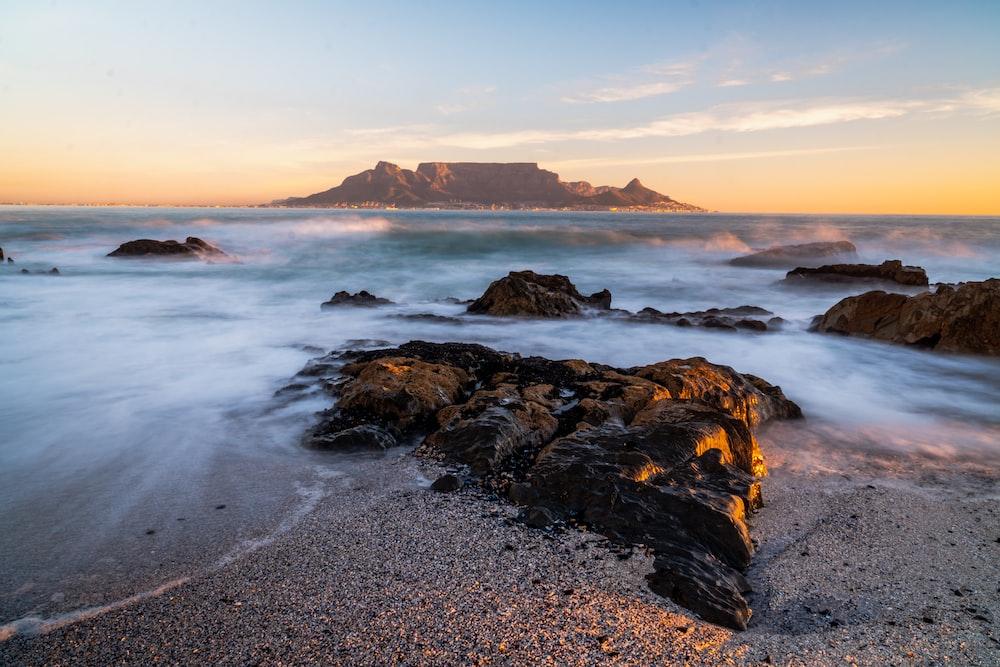 water splashing on shore rocks overlooking island at the horizon
