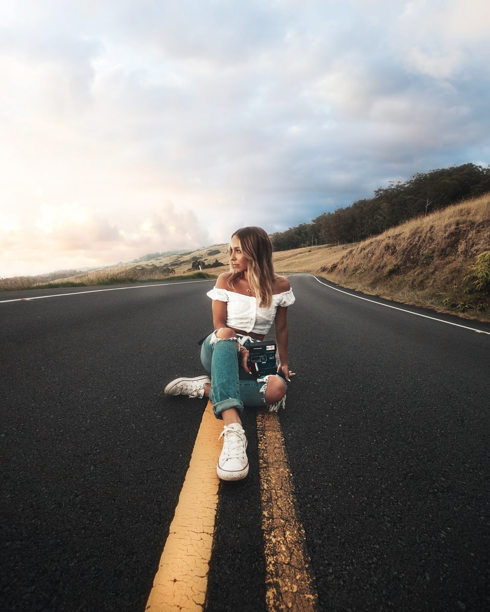 woman sitting on highway