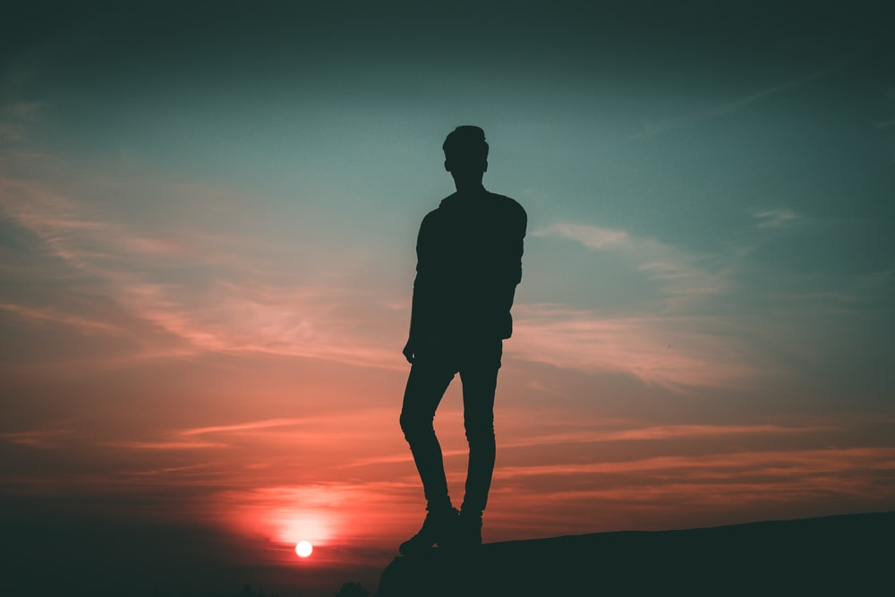 silhouette of man standing during twilight