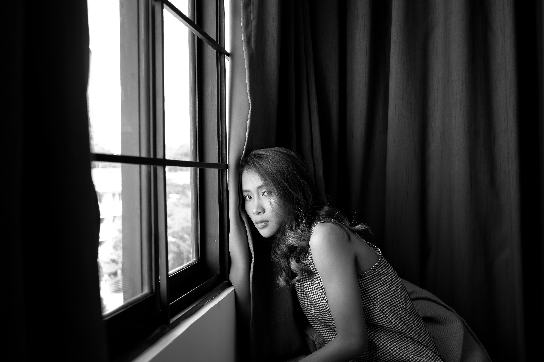 woman near wall grey-scale photo
