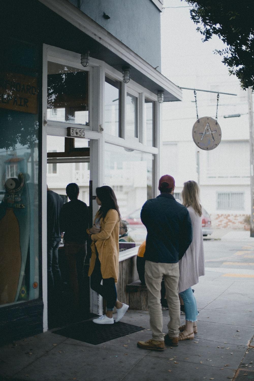 three people standing near glass door