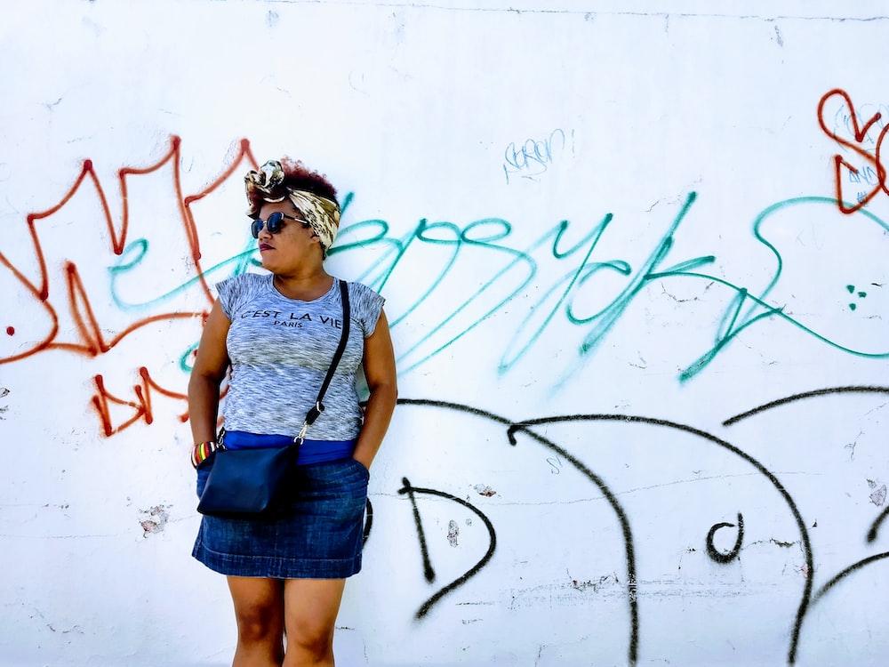 woman wearing gray crew-neck cap-sleeved shirt and blue denim mini skirt standing near graffiti wall during daytime