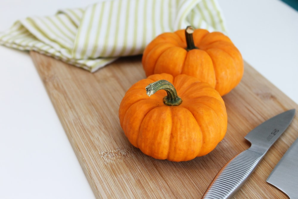 selective focus photography of two pumpkins placed on chopping board