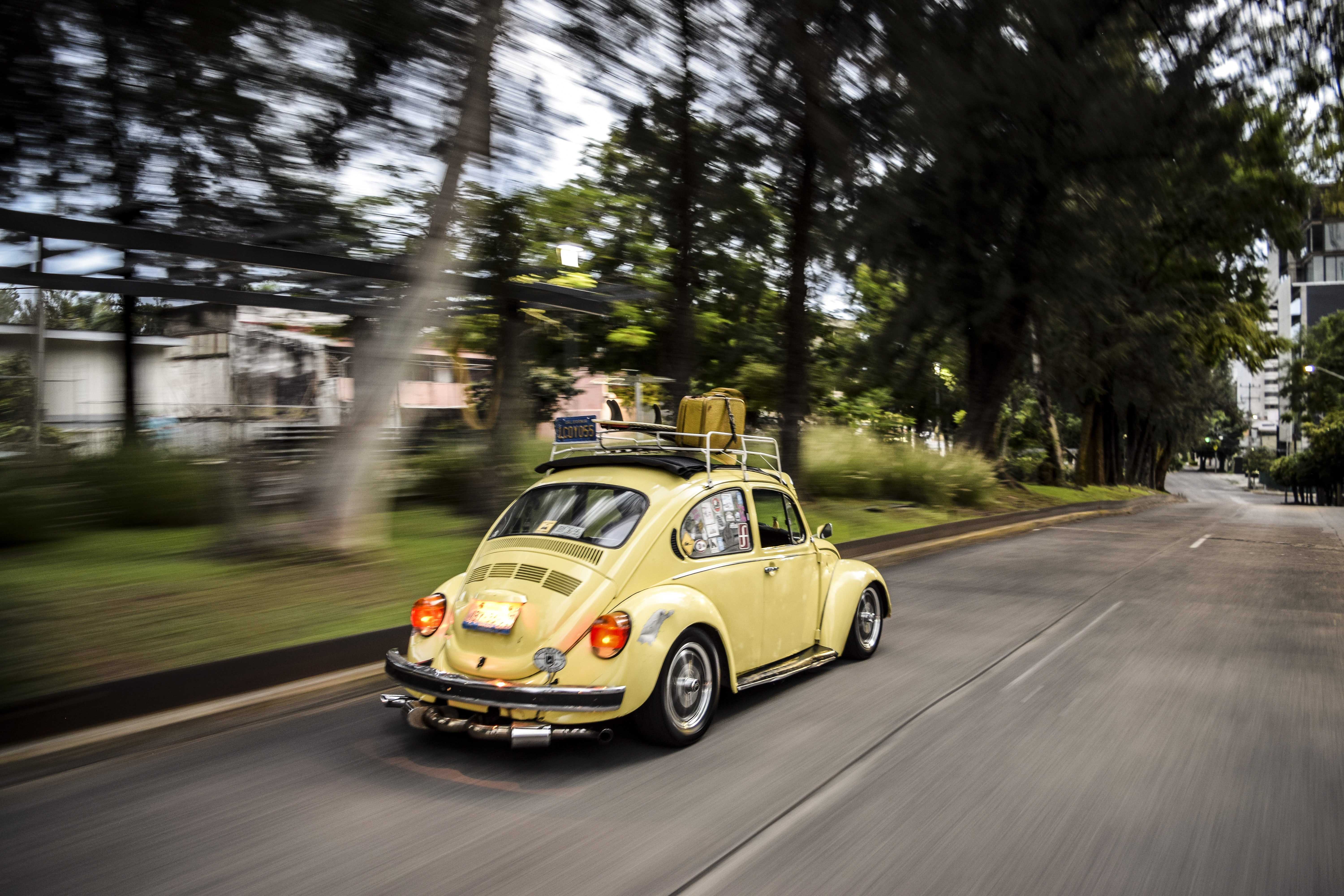 time lapse photo of running yellow Volkswagen Beetle coupe on road