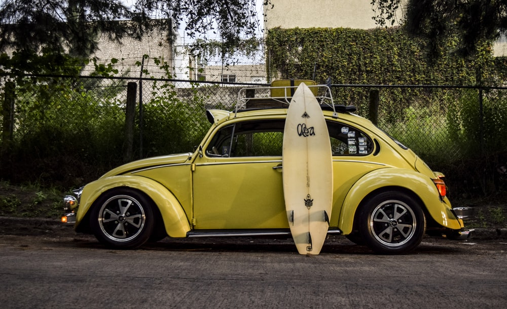 surfboard leaning on yellow car
