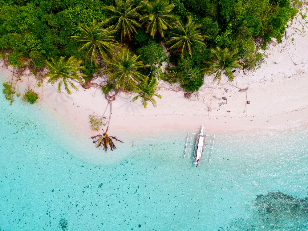 bird's-eye photography of boat on island