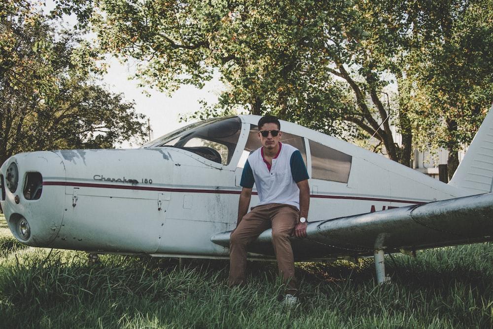 man sitting on biplane wing