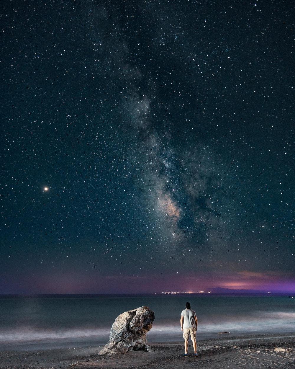man standing near rock viewing calm sea