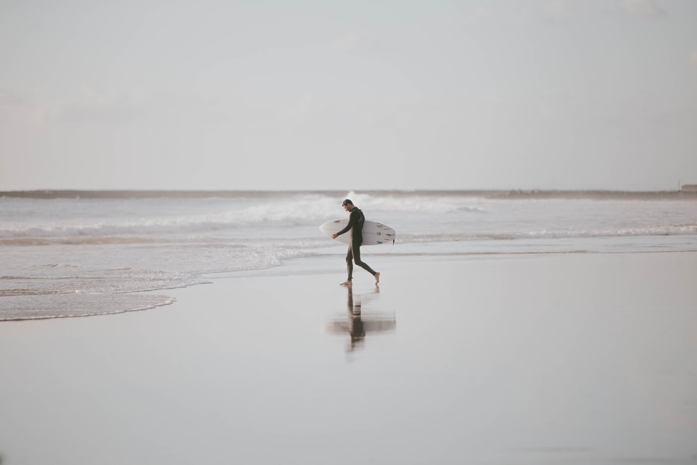man holding surfboard walking in the beach during daytime