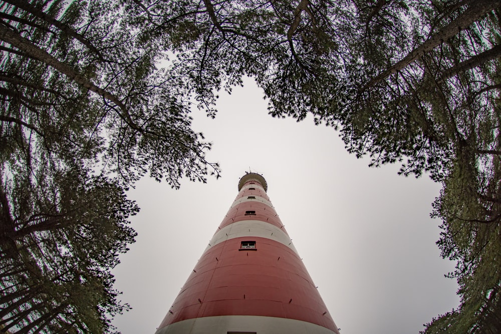 low angle photo of white and red lighthouse