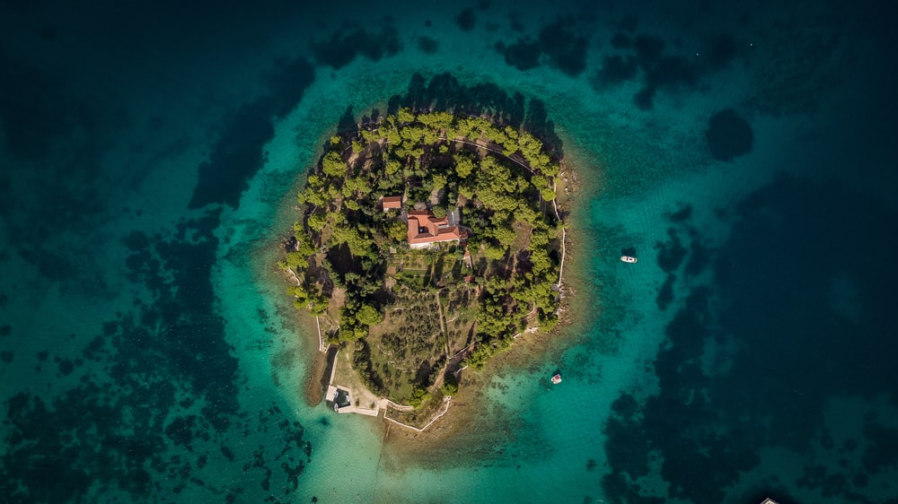 aerial photography of island surrounded by sea during daytime