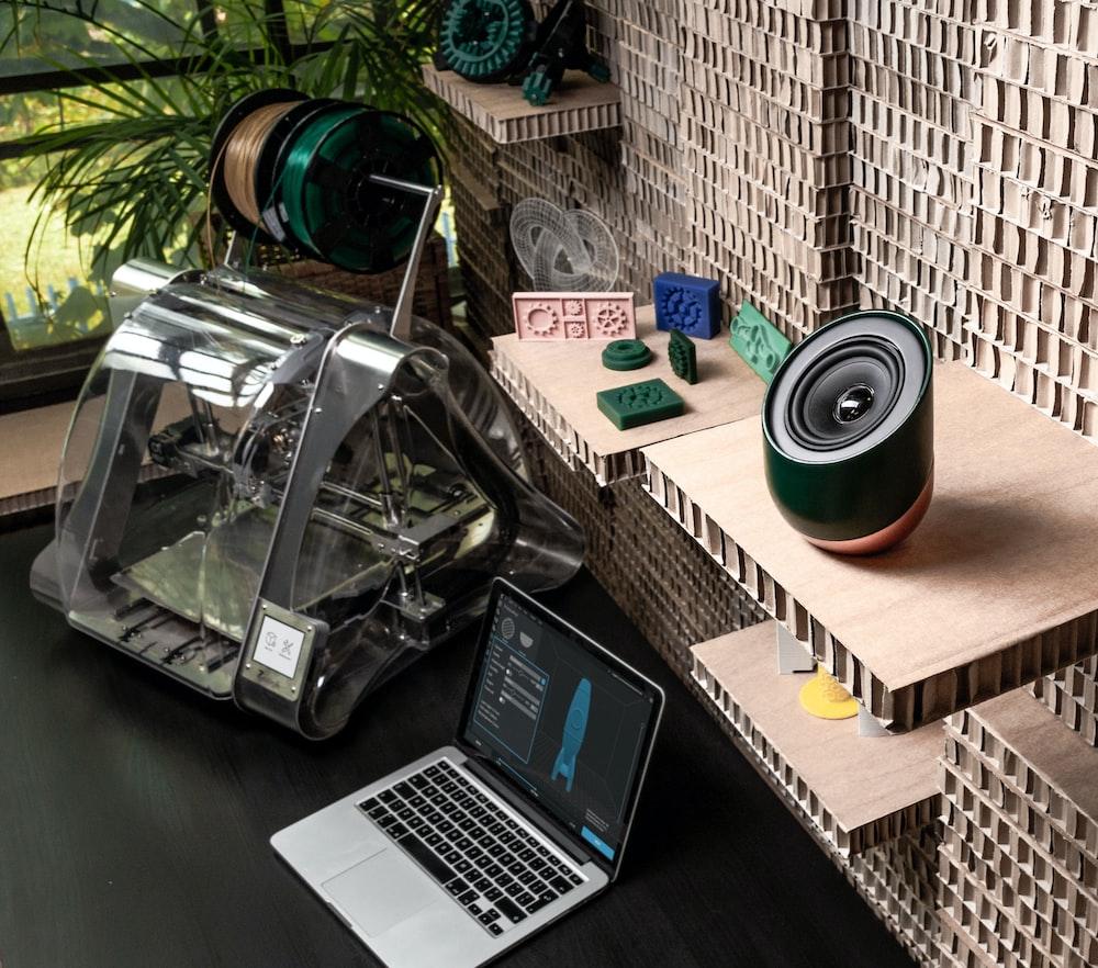 MacBook Pro beside 3D printer near black speaker on gable