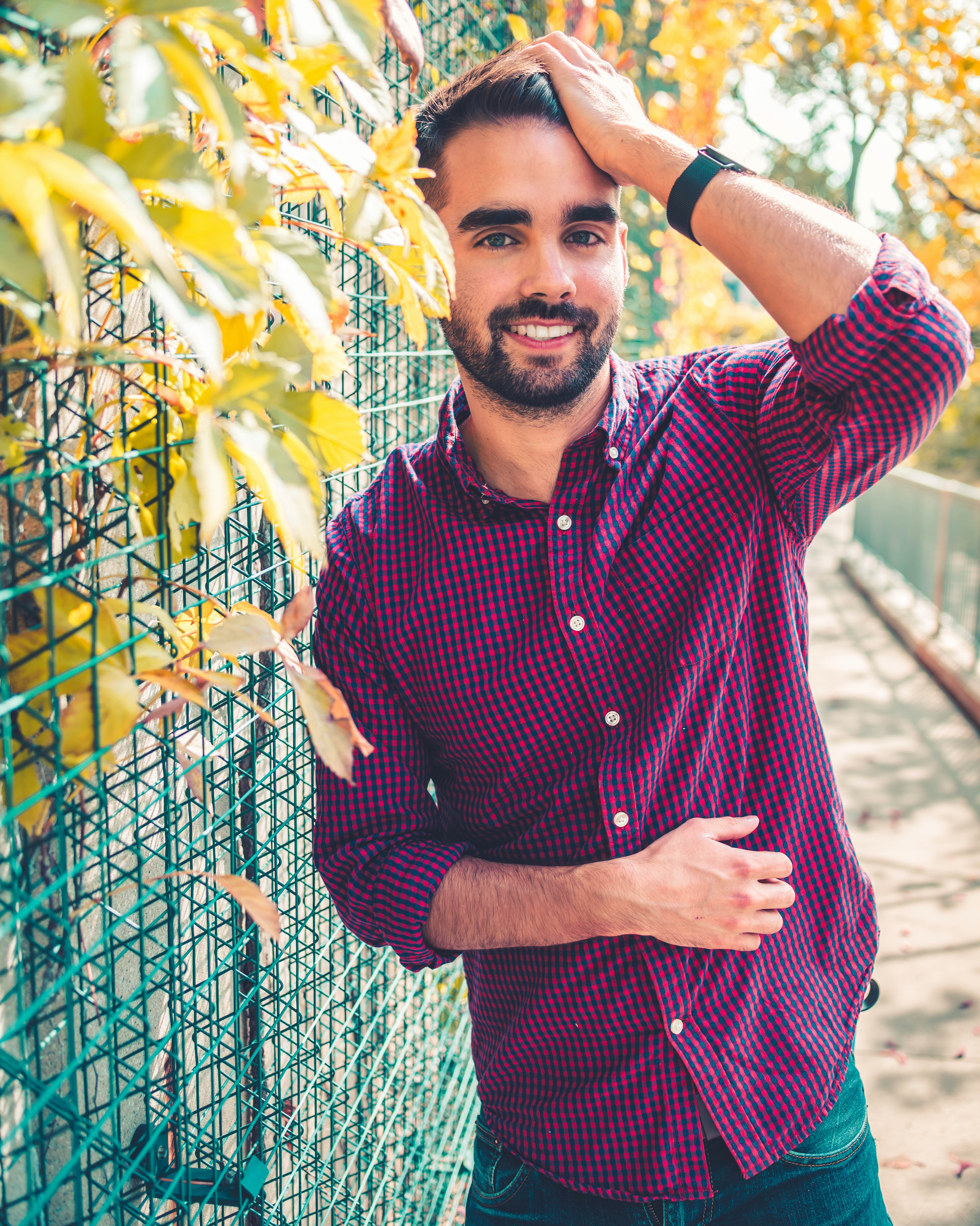 smiling man standing beside green screen fence with green plants durng daytime