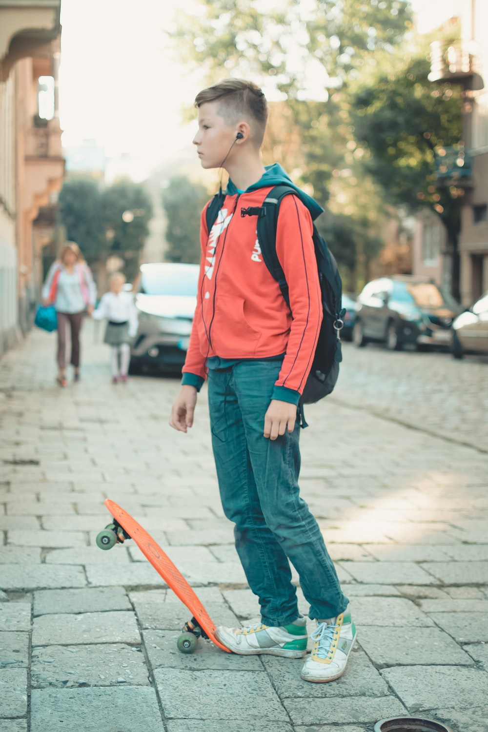 boy with backpack and earbuds standing near orange skateboard