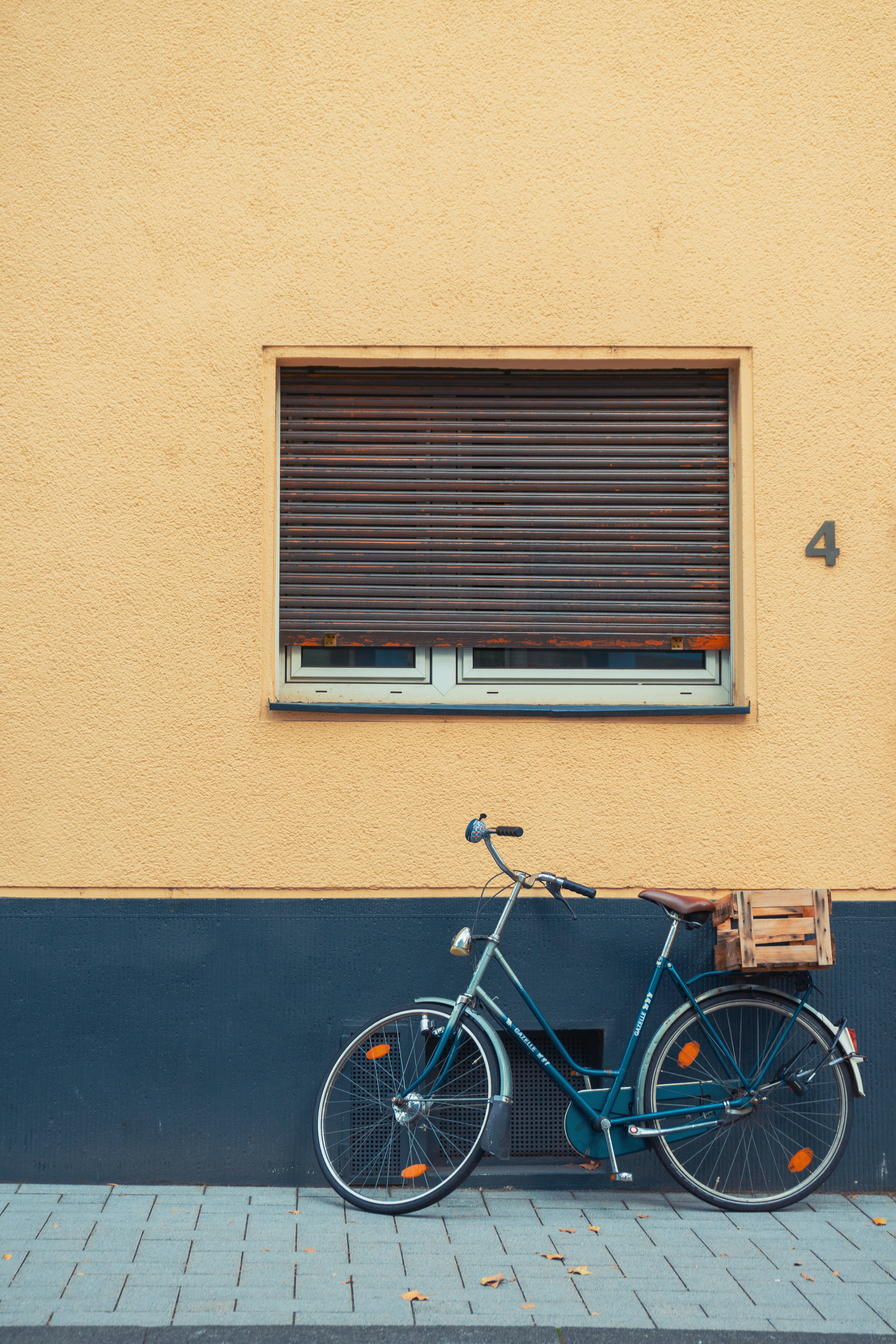 blue step-through bike leaning on wall