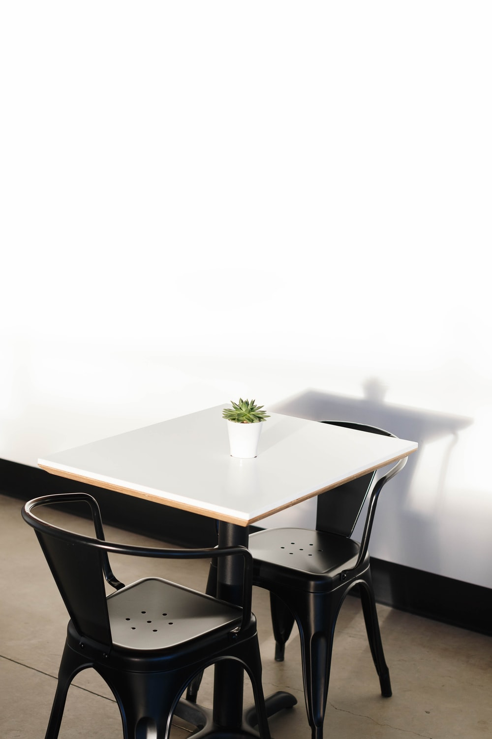 square white wooden table with two black chairs