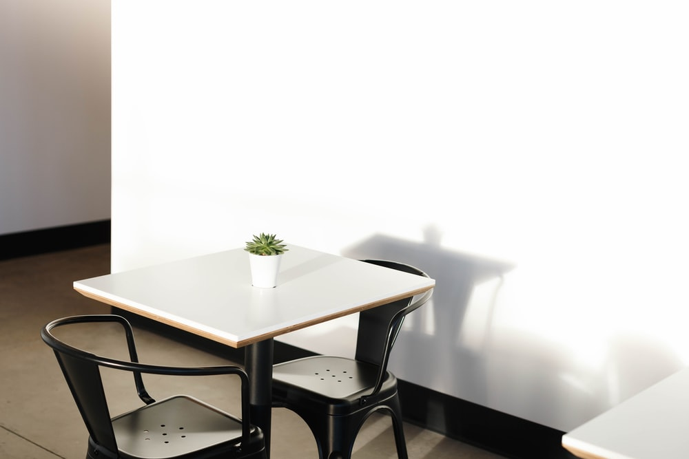square white wooden table with two black metal chairs