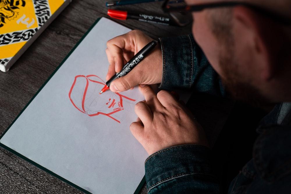 man drawing on white printer paper