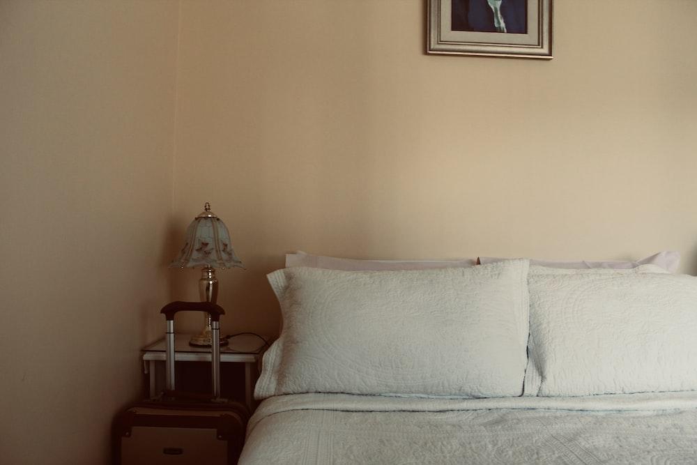 white bed beside wooden nightstand inside room