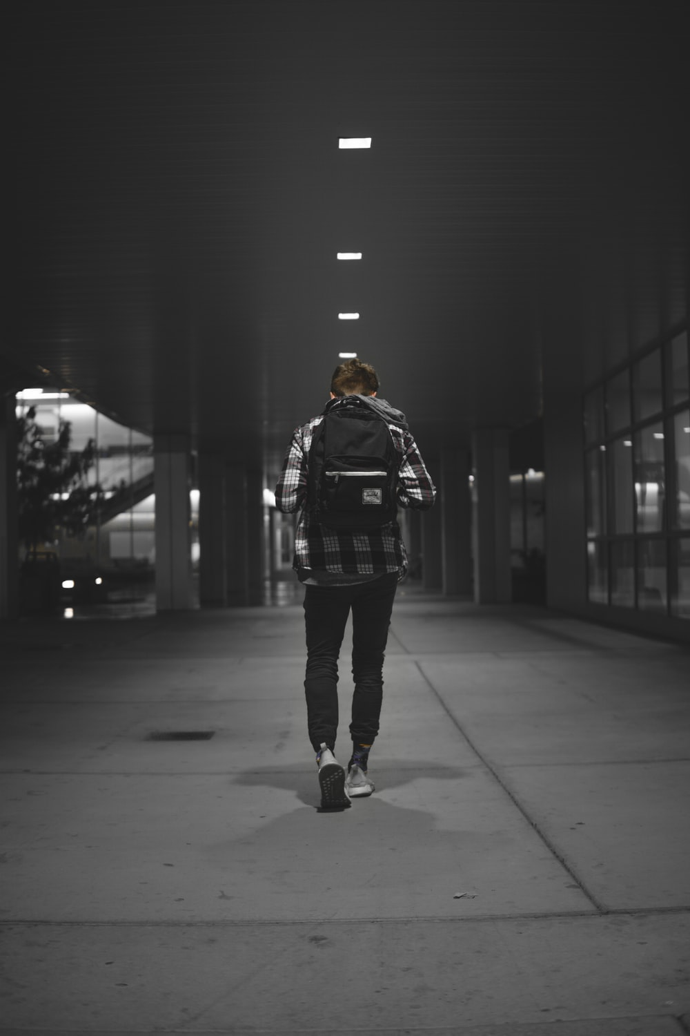 man with backpack walking alone on pathway