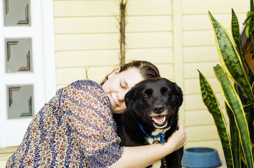woman hugging black dog