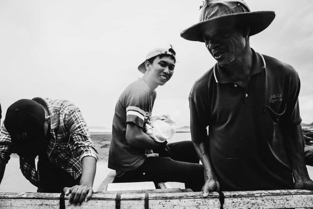 three men standing near railing