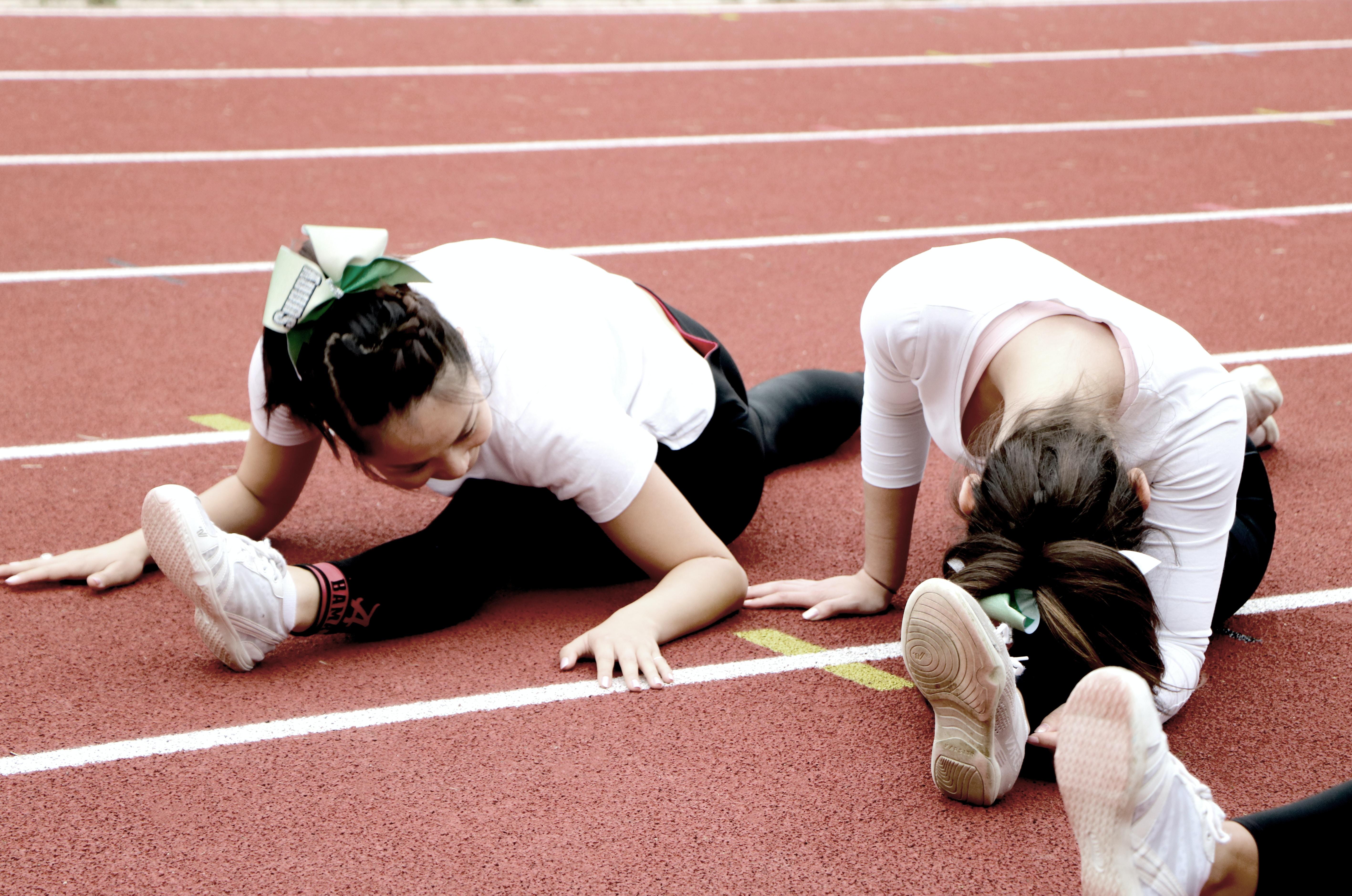 two women splitting legs on running track