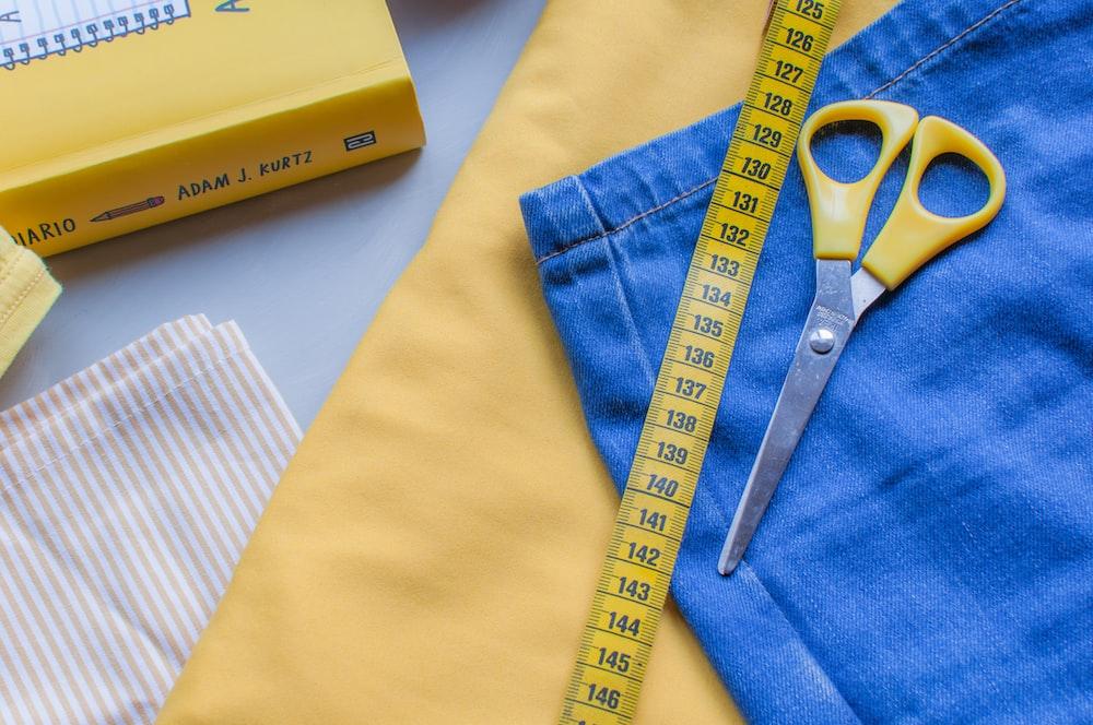 yellow scissors on blue denim cloth