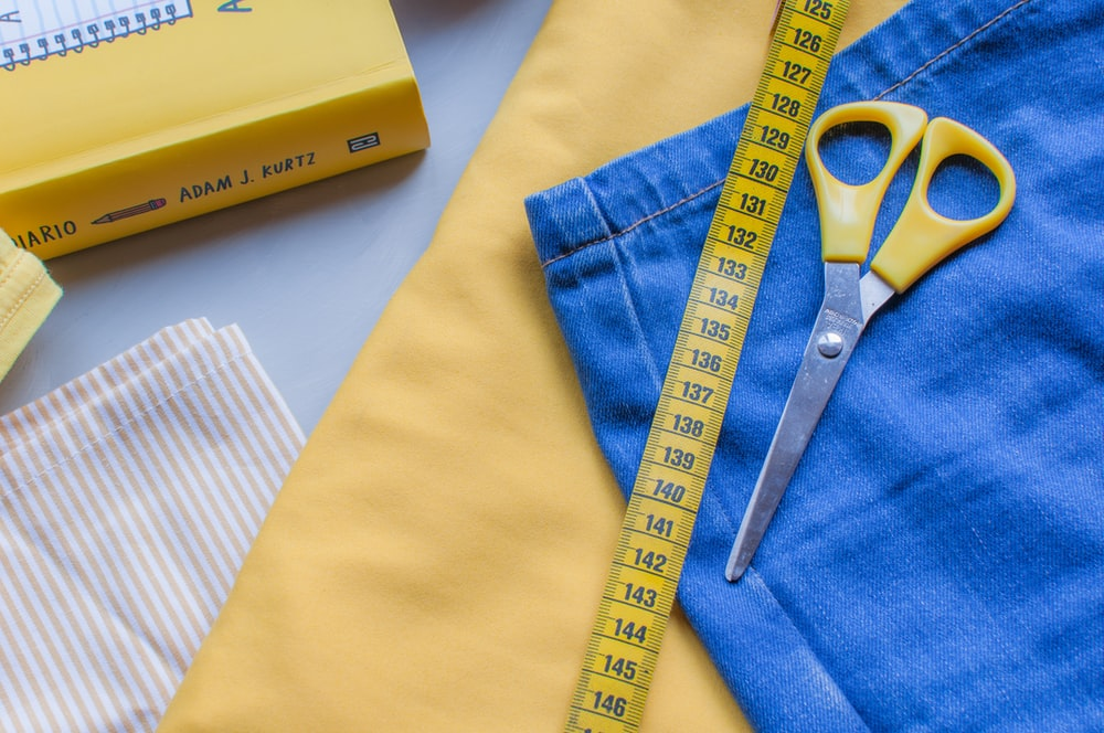 yellow scissors on blue denim cloth