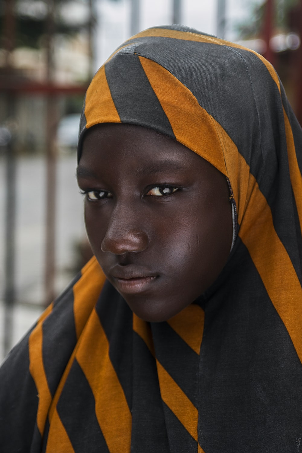 girl in black and orange striped head scarf in selective focus photography