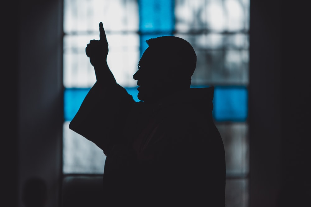 silhouette of man standing near stained glass window