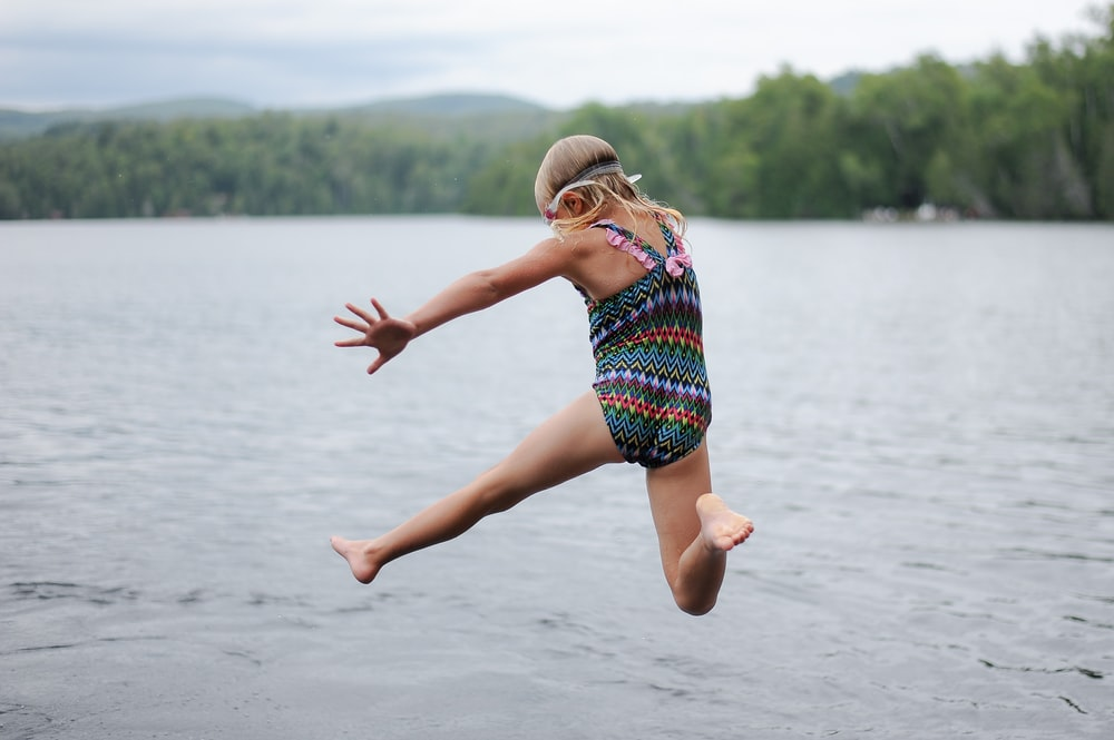 girl skipping on body of water