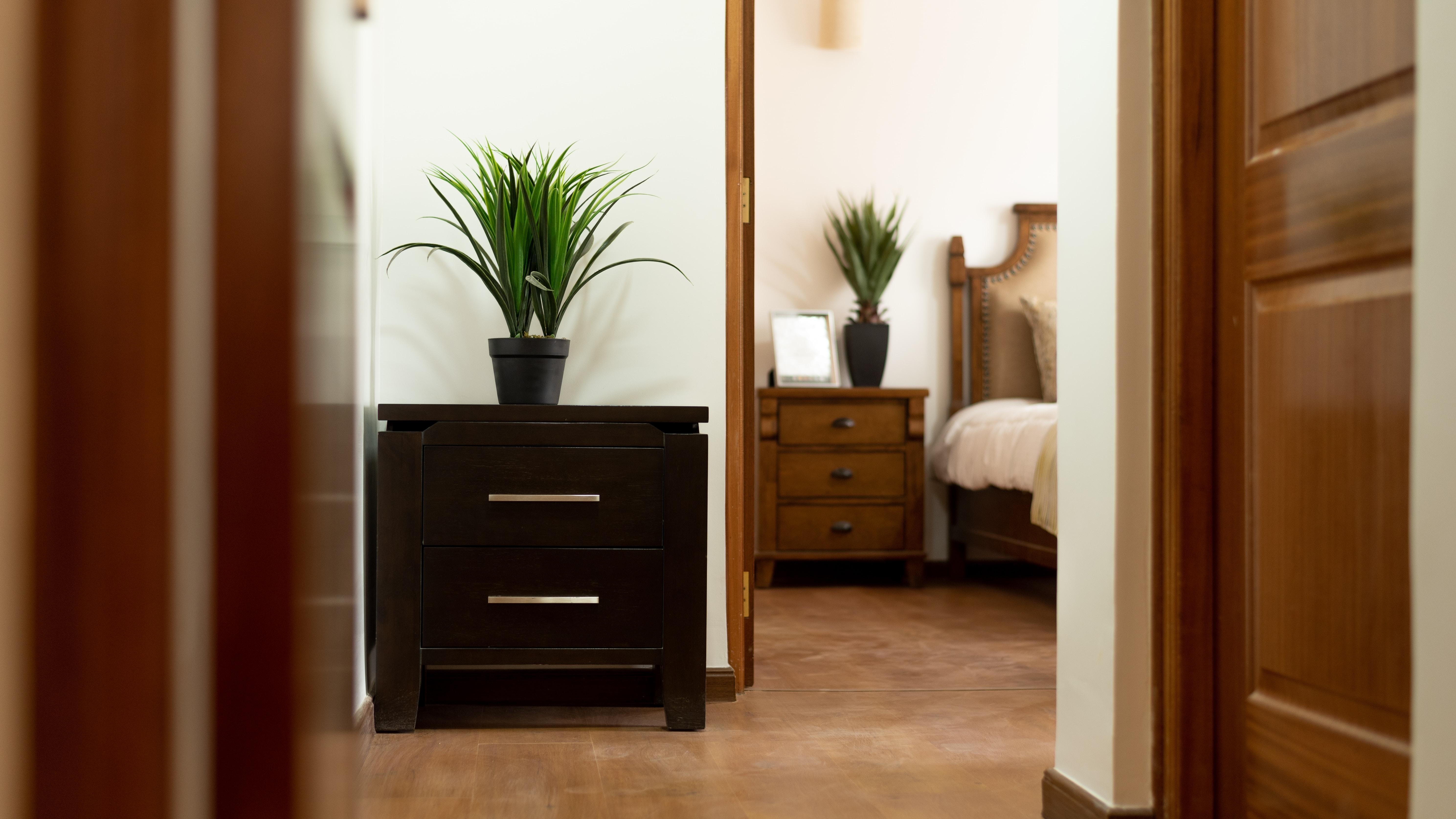 brown wooden nightstand beside doorway inside room