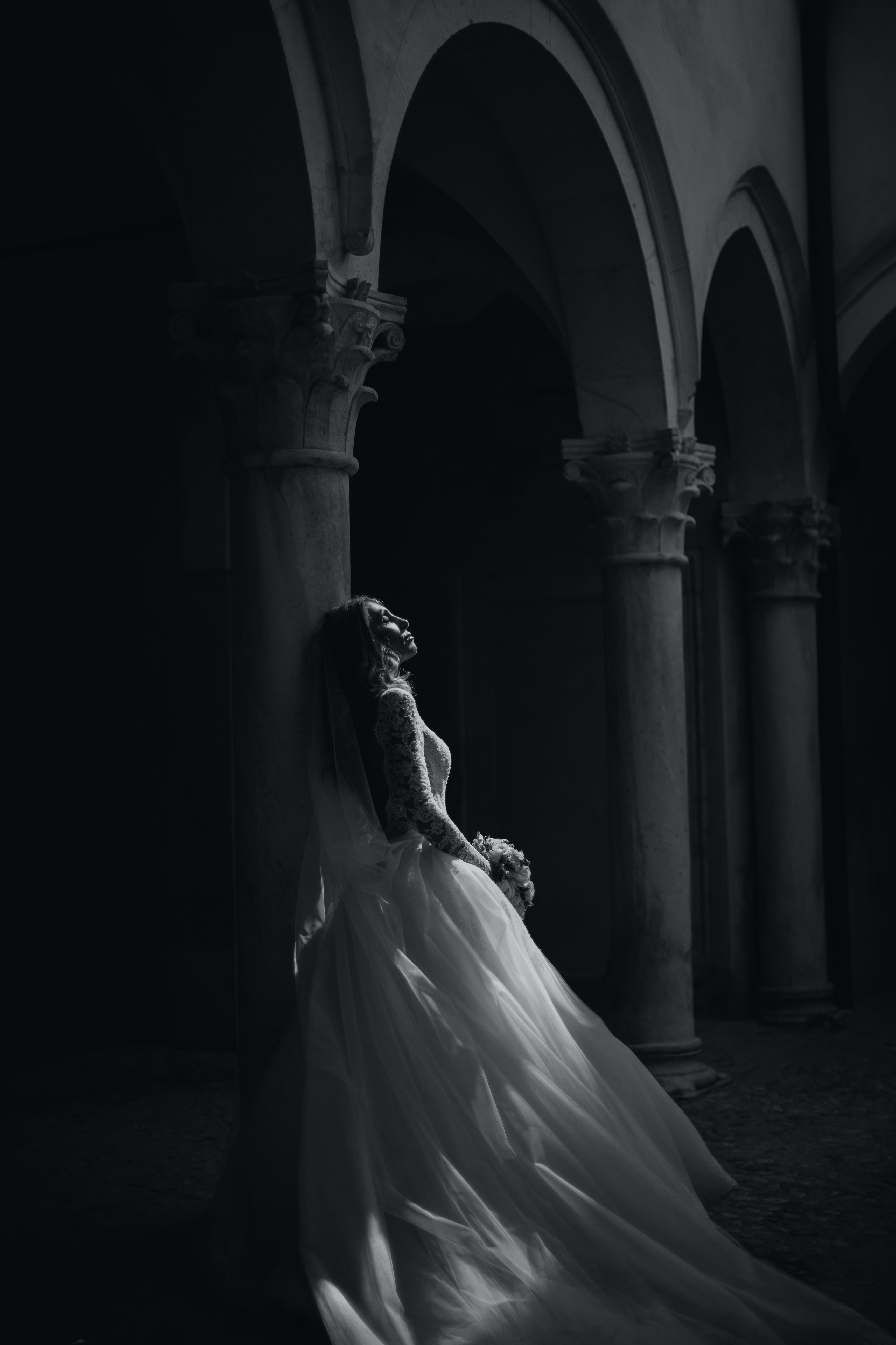 woman standing beside pillar