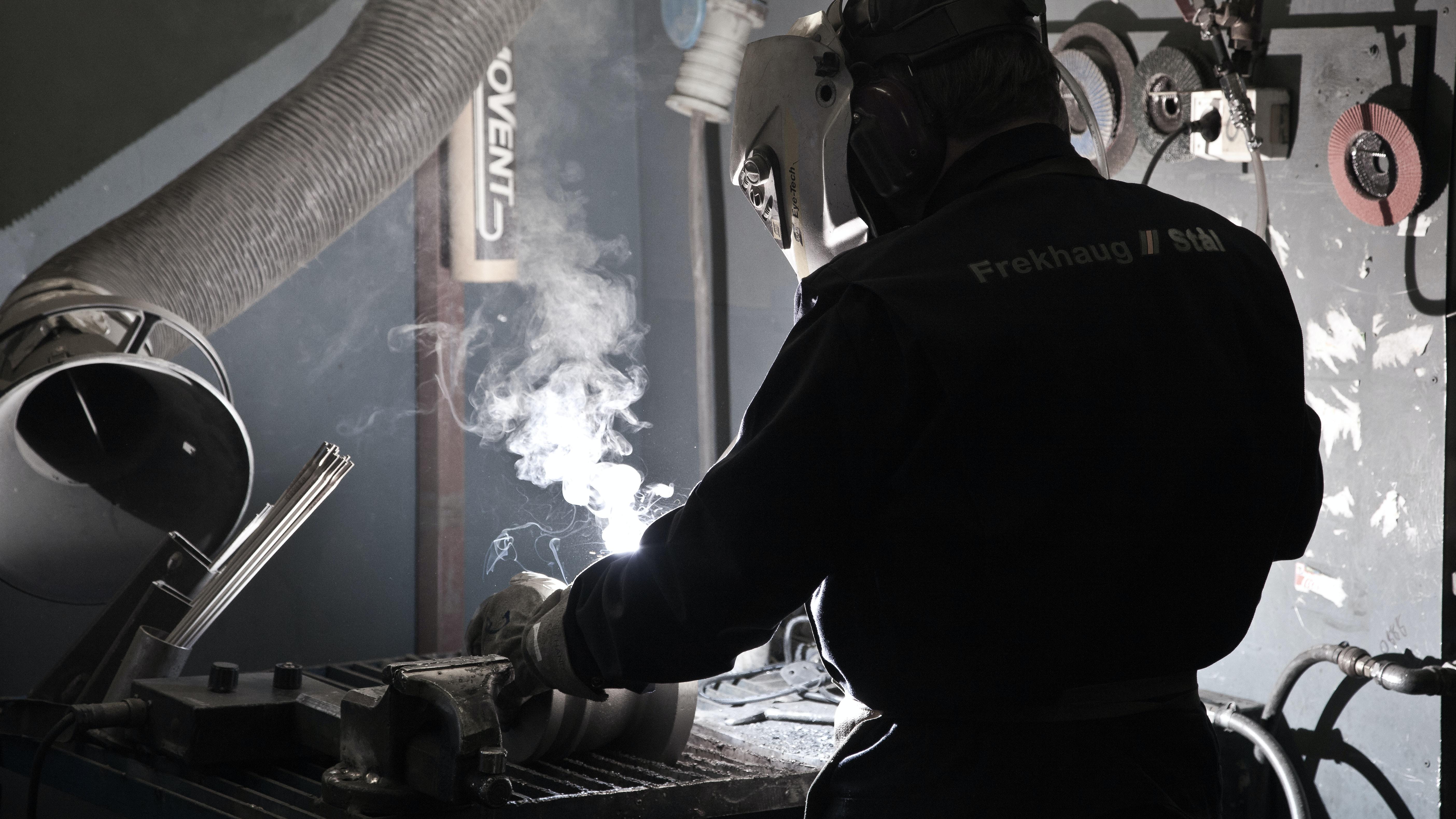man in working suit welding metal