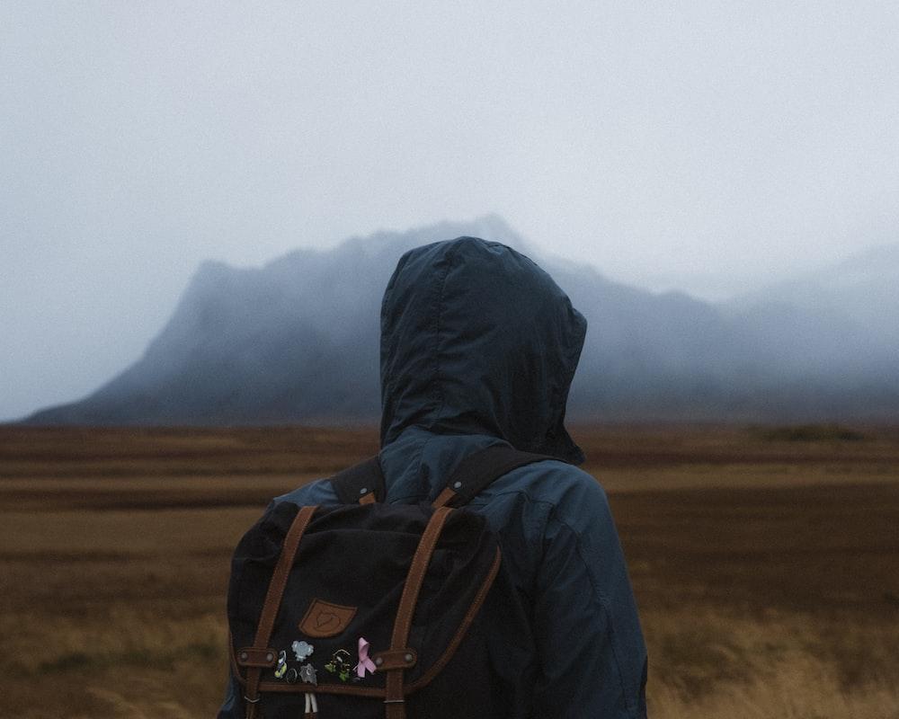 man carrying black knapsack