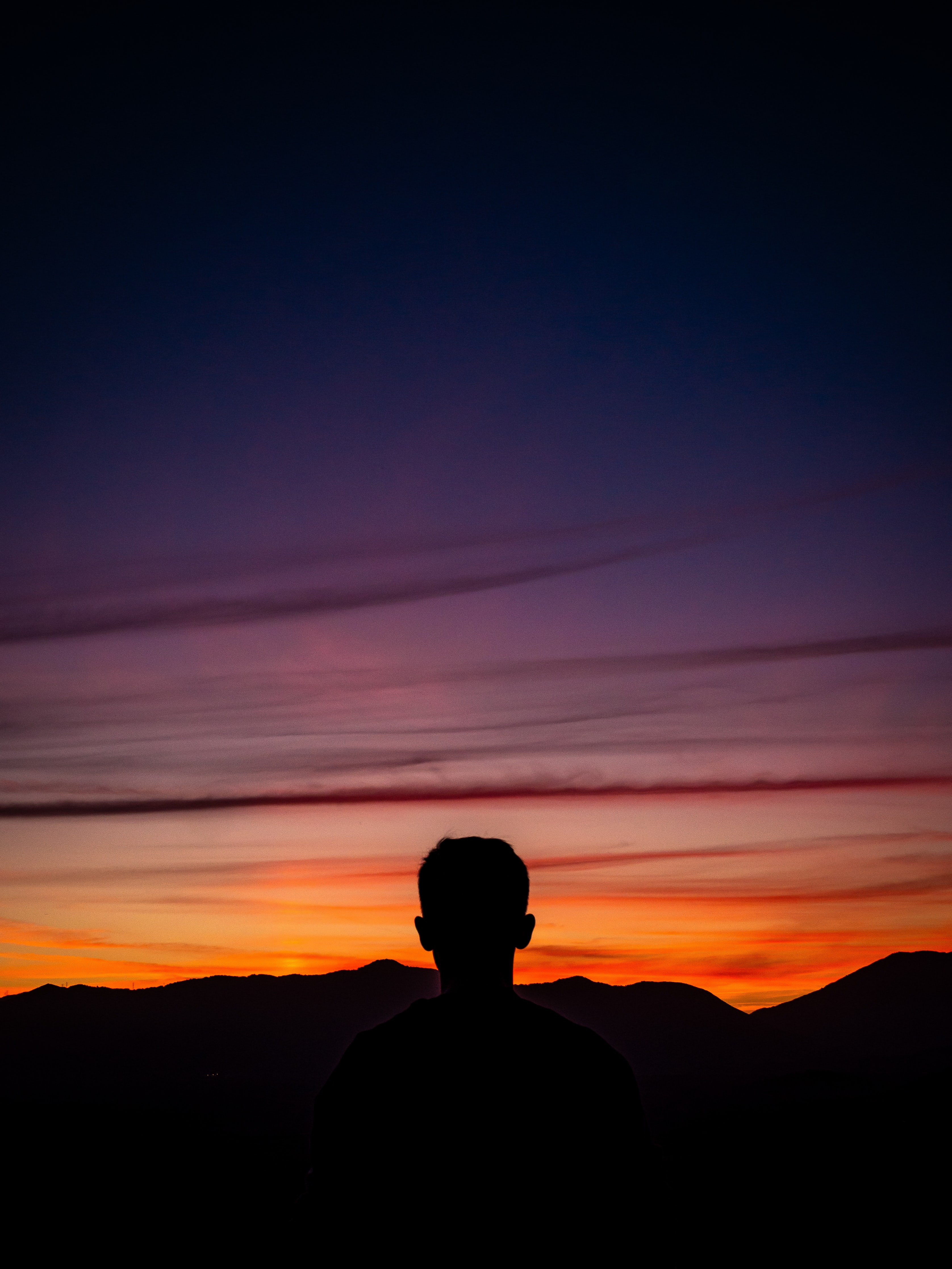 silhouette of man standing with mountain on horizon