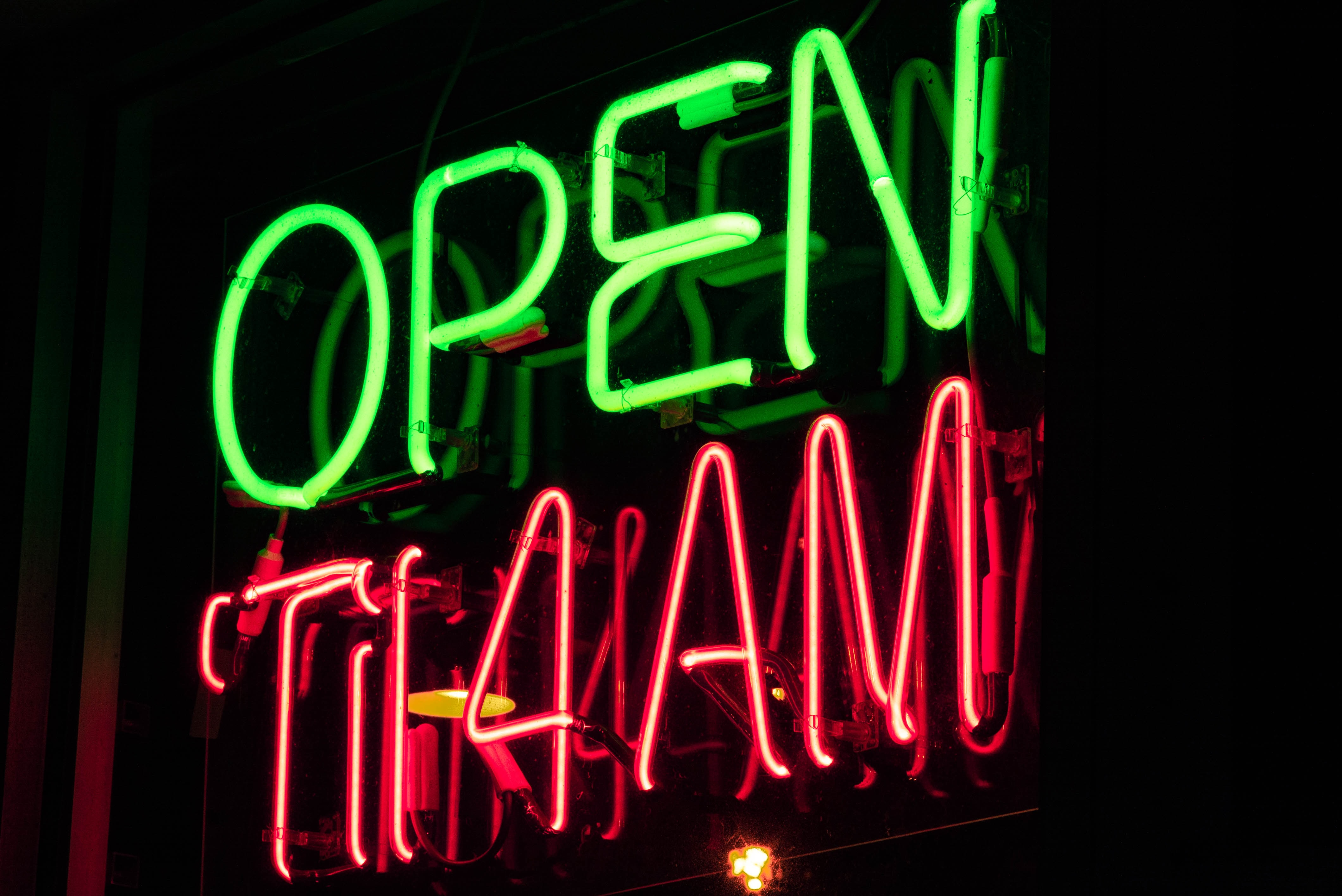 low-light photo of open til 4 AM neon sign