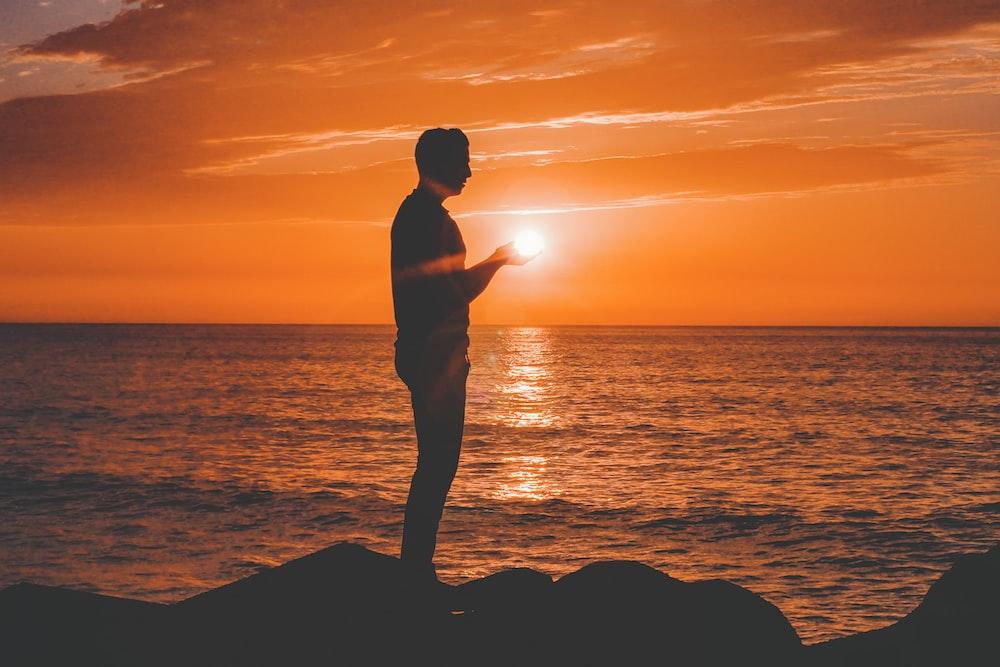 silhouette of man standing near sea shore