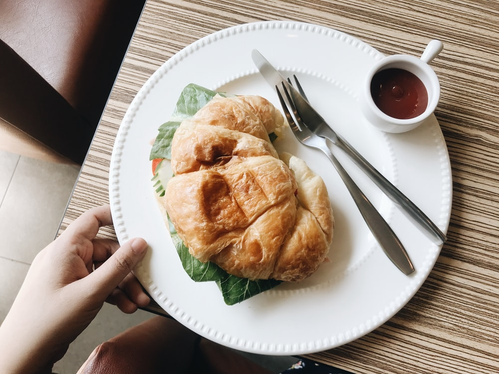 croissant on plate with spoon and fork and small white ceramic cup with sauce on table