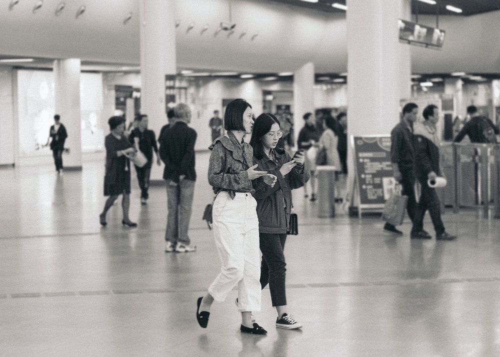 two women walking while holding phone