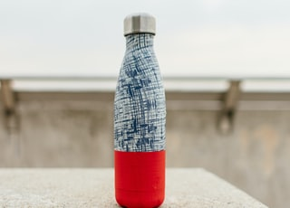 gray and red bottle on white concrete surface
