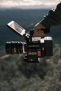 man holding black professional camcorder