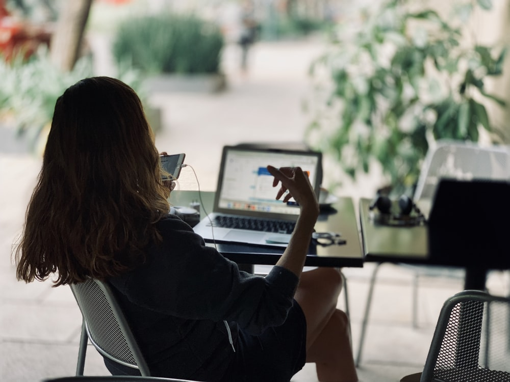 woman sitting on chair in front of table with laptop